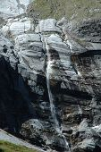 Waterfall In Rocky Valley Nearby Grindelwald In Switzerland