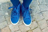 Blue tennis shoes on a stone background