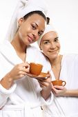 Two women in wellness salon dressed in white robes