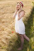 Cheerful Beautiful Young Blonde Girl In White Dress With Straw Hat Posing At Golden Wheat Field