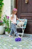 Outdoor portrait of a cute little girl petting a cat
