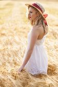 Lonely Beautiful Young Blonde Girl In White Dress With Straw Hat Walking At Golden Wheat Field