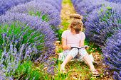 Little girl reading a book in lavender field