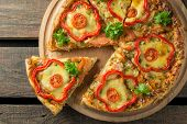 Pizza with pepper and chicken on a wooden background