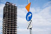Three traffic signs are seen on the pillar in front of the abandoned skyscraper