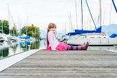 Outdoor portrait of adorable little girl resting by the lake