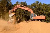 pic of track-hoe  - Large track hoe excavator loading a articulated dump truck with dirt from a new commercial development construction project - JPG