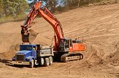 foto of dump_truck  - Track hoe excavator filling up a dump truck at a new commerical construction development - JPG