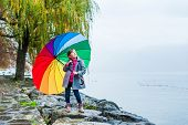 Little girl outdoors with colorful umbrella