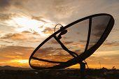 Satellite Dish On Sunset Sky Background.