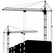 Silhouette of two cranes working on the building