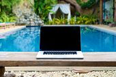 stock photo of bench  - Laptop on a bench by the pool working on vacation with mobility concept