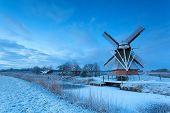 Dutch Windmill On Snow In Winter Dusk