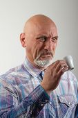 stock photo of disgusting  - Portrait of a man drinking a coffee disgusting - JPG