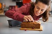 Closeup On Happy Young Housewife Decorating Freshly Baked Pumpkin Bread With Seeds