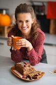 Happy Young Housewife Drinking Tea With Freshly Baked Pumpkin Bread With Seeds