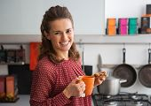 Portrait Of Happy Young Housewife Drinking Tea With Freshly Baked Pumpkin Bread With Seeds