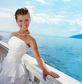 image of fancy-dress  - Beautiful bride wearing a fancy wedding dress looking at camera in the sunny day at the water view - JPG