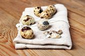 Quail Eggs And A Napkin Lying On A Wooden Table