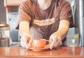 Barista Offering Mini Orange Cup Of Coffee