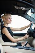 Beautiful young woman driving car