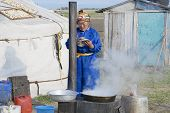Woman cooks in front of the yurt entrance circa Harhorin, Mongolia.