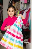 Little Girl Picking Out A Dress From The Closet