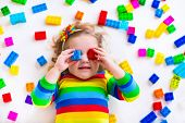 stock photo of daycare  - Cute funny preschooler little girl in a colorful shirt playing with construction toy blocks building a tower in a sunny kindergarten room - JPG