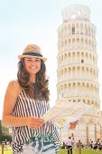Portrait Of Smiling Young Woman With Map In Front Of Leaning Tower Of Pisa, Tuscany, Italy