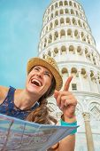 Young Woman With Map Pointing In Front Of Leaning Tower Of Pisa,