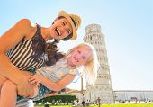 Portrait Of Mother And Baby Girl In Front Of Leaning Tower Of Pisa, Tuscany, Italy