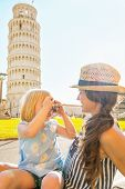 Baby Girl Taking Photo Of Mother In Front Of Leaning Tower Of Pisa, Tuscany, Italy