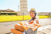 Closeup On Young Woman Giving Pizza In Front Of Leaning Tower Of
