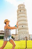Funny Young Woman Supporting Leaning Tower Of Pisa, Tuscany, Italy
