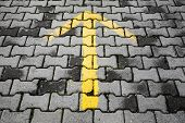 Yellow Arrow Painted On Dark Gray Cobblestone Pavement