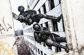 stock photo of roping  - Spec ops police officers SWAT during rope exercises with weapons