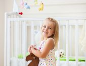 image of wooden horse  - Little cute girl in nursery room with toys and wooden horse - JPG
