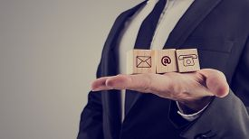 pic of communication  - Retro style image of a businessman holding three wooden cubes with contact symbols  - JPG