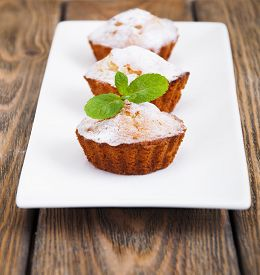 foto of bakeshop  - Homemade Muffins Ready for Breakfast on a plate on wooden background - JPG