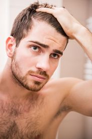 pic of male pattern baldness  - Handsome man is checking hairline while looking at the mirror - JPG