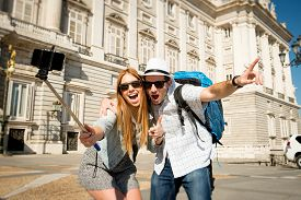 foto of selfie  - young beautiful friends tourist couple visiting Spain in holidays exchange students and taking selfie stick picture together in town happy on sunny day in travel and vacation concept - JPG