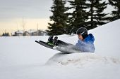 image of toboggan  - Winter Fun - Child Sledding/Tobogganing Fast Over Snow Ramp ** Note: Visible grain at 100%, best at smaller sizes - JPG