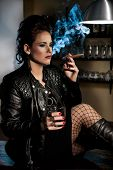 stock photo of peer-pressure  - Woman dressed in black leather jacket sitting on the bar smoking a cigar and drinking alcohol - JPG