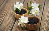 foto of jasmine  - Dry black jasmine tea with jasmine flowers in wooden bowls on a wooden background - JPG