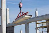 picture of crane hook  - Concrete slab hanging from crane hook above building skeleton at construction site - JPG