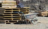 picture of wooden pallet  - Old wheelbarrow standing next to wooden pallets at construction site - JPG