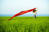 image of rune  - Young lady runing with tissue in green field - JPG