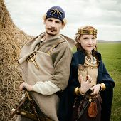 stock photo of armor suit  - woman and man in ethnic suit context of historical reconstruction - JPG