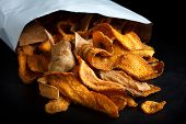 image of parsnips  - Open packet of fried parsnip and carrot chips on black - JPG