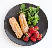 picture of eclairs  - French eclair strawberry and mint on black plate - JPG